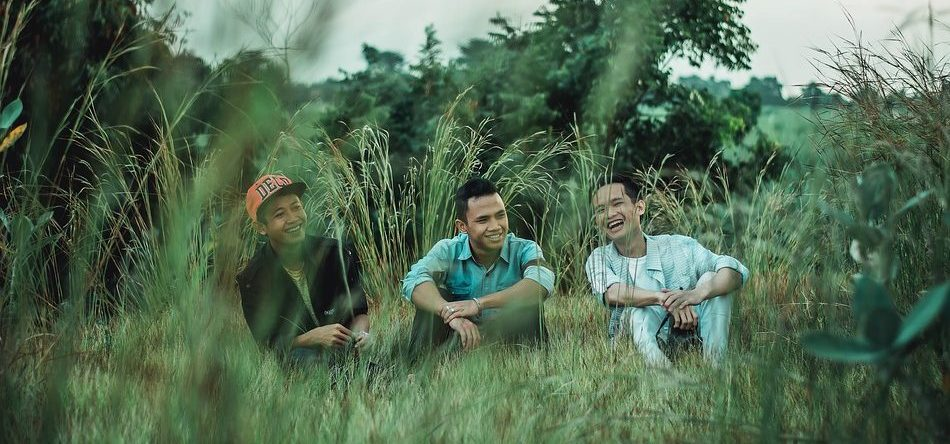 Three men sitting together in a field laughing.